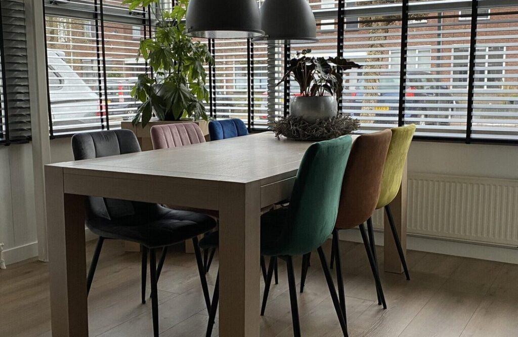Verschillende kleuren eetkamerstoelen rond een tafel